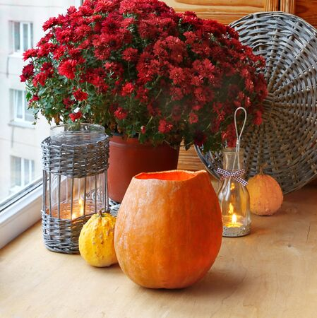 Bunch of red chrysanthemums and pumpkins with an  lantern-candlesticks on a window.  photo