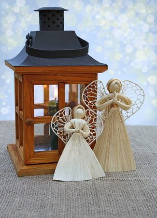 conflagrant: Handmade christmas decoration angels from straw and lantern with a conflagrant candle. Products of mass production. Stock Photo
