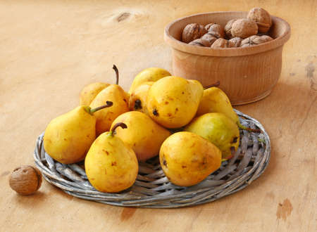 Yellow pears and bowl of walnuts on a wooden table Stock Photo