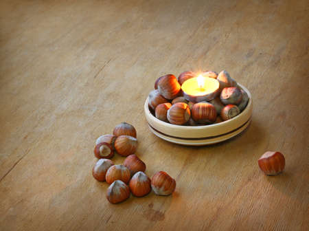 conflagrant: Conflagrant candle and hazel on a wooden table Stock Photo