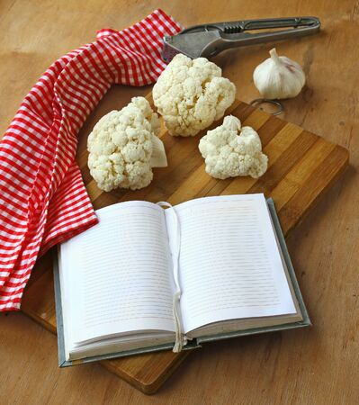 Notebook for recipes with raw vegetables ingredients on a wooden chopping board. photo