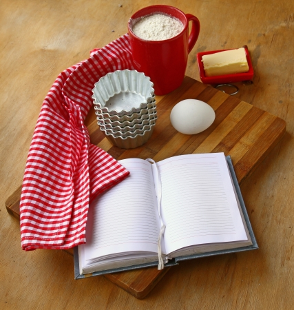 Open notebook with a towel, butter, cup of flour, egg and piepans photo