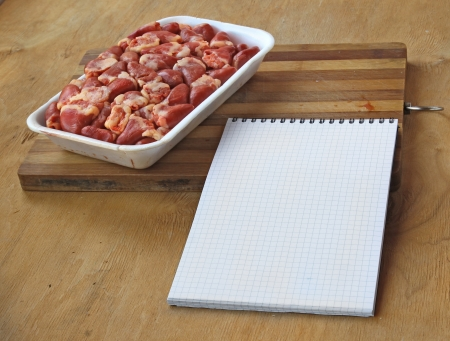 inwards: Notebook for recipes with raw raw chicken hearts on a kitchen