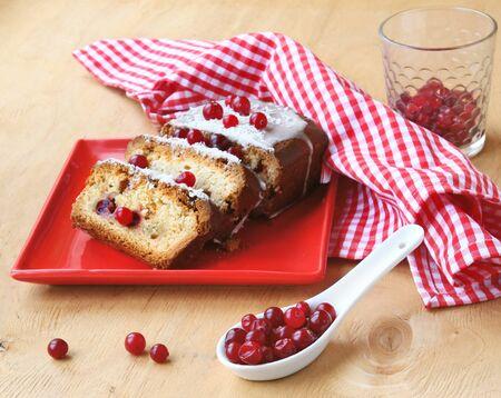 나무 테이블에 빨간 접시에 크리스마스 크랜베리 케이크