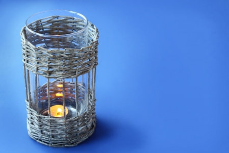 scintillating: Age-old wattled lamp  a with a burning candle on a dark blue background Stock Photo