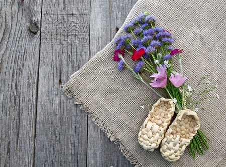 Rural still life with decorative sandals made of bark and with a bouquet of wild flowers on a wooden table photo