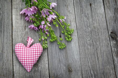 musk: Rustic still life with a bouquet of pink mallow and heart on a wooden background