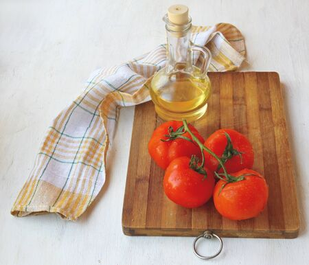 Bunch of tomato on the board next to the bottle of olive oil on the table photo