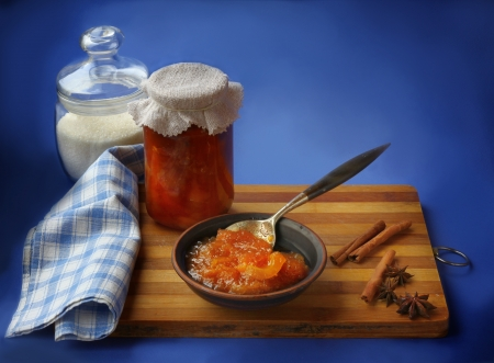 Jar of homemade jam from a quince and jar with sugar on a wooden table photo