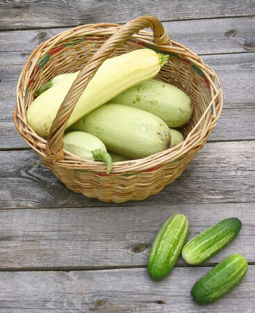 Basket with fresh zucchini and cucumber on a wooden table Stok Fotoğraf