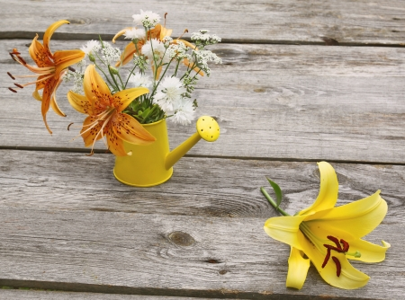 Bouquet of yellow and orange lilies in a watering can on a wooden table Imagens
