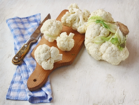 Cauliflower on the chopping board and kitchen knife Imagens