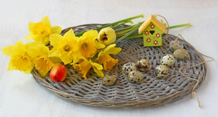 Easter composition of a bouquet of spring flowers, quail eggs and decorative  birdhouse on a wicker round photo