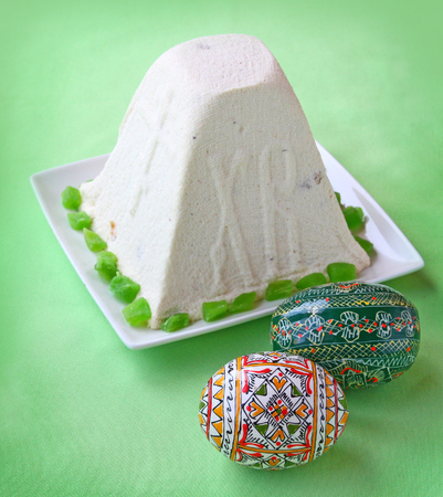 paskha: Curd paskha  pacha  and decorative Easter eggs on a green background  Products of mass production in the the national traditions Stock Photo