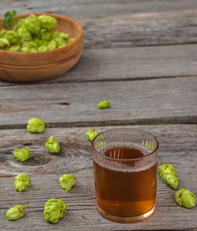 ingredients tap: Harvest of hops and a glass cup with a drink from the hops on a wooden table