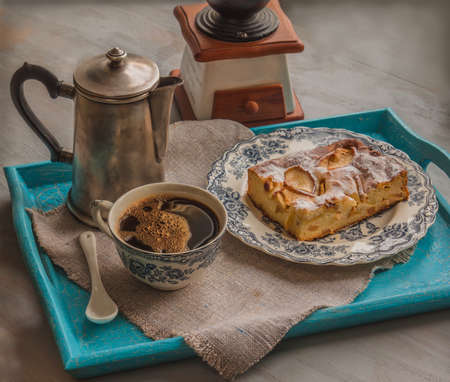 Vintage cup of hot coffee and cheesecake in a blue tray on a gray table