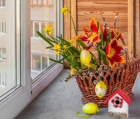 Basket with tulips and daffodils on the windowsill. Easter decoration photo