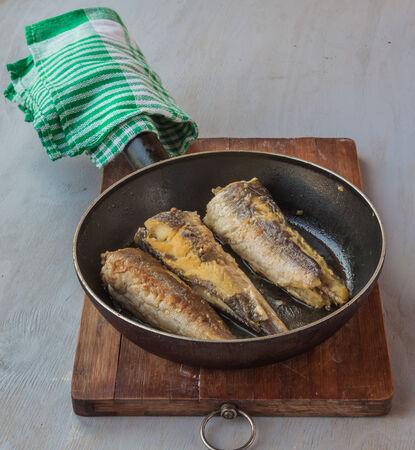 pescado frito: Merluza frita en una sart�n en la tabla de cortar en la mesa de la cocina