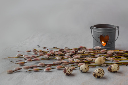 Pussy willow bunch with the candlestick burning candle on wooden background and quail eggs   photo