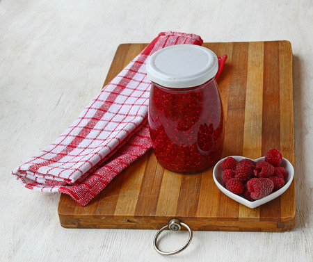 Raspberry on a background of jars of jam on a kitchen cutting board photo