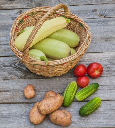 Basket with tomatoes, cucumbers, zucchini, potatoes on a wooden table photo