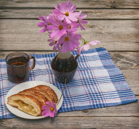 Strudel with apples and a cup of tea next to a bouquet of cosmos on a wooden table photo