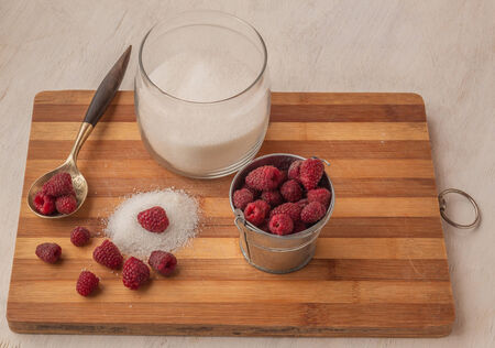 Raspberry on a background of  sugar on a kitchen cutting board photo