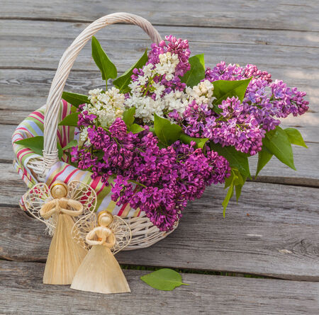 Basket with a bouquet of lilacs and two angels of straw on a wooden table photo