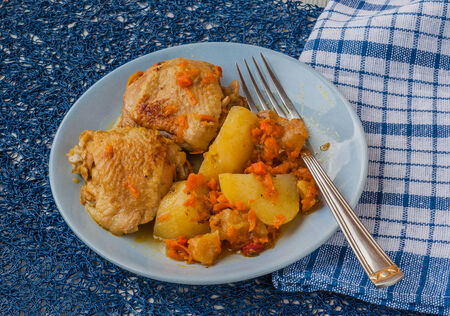 Dinner of chicken with apples, potatoes and carrots on a plate in Armenian photo