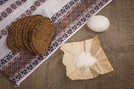 Still life with rye bread, salt and bast shoes on an embroidered towel