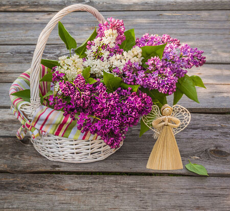 White basket with a branch of lilac and angel made ​​of straw on a wooden table on a sunny spring day photo