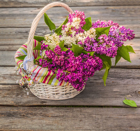 White basket with a branch of lilac and heart on a wooden table on a sunny spring day photo