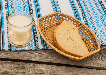 Glass of milk and portioning pieces of white bread in a breadbox on embroidered tablecloth photo