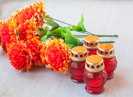 Four gravestones red glass candlestick and branch of artificial flowers on a gray wooden background photo