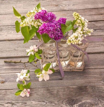 Beautiful Bunch of Lilac with blooming branch of apple on a wooden background photo