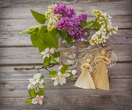 Beautiful Bunch of Lilac with angels on a wooden background photo