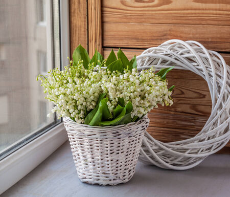Basket with lilies of the valley (Convallaria majalis) next to angel on o the window photo