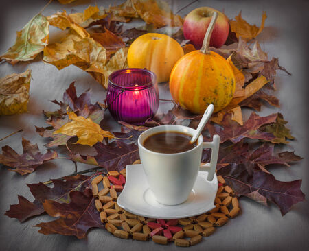 Cup of coffee on a wooden table with fallen leaves, burning candle and pumpkins photo