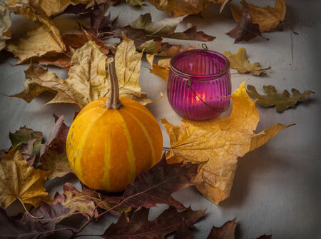 Glass candle holder with burning candle and pumpkin  near the leaves photo
