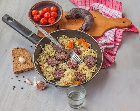 Ein Stück Blutwurst mit Reis in der Pfanne mit einer Scheibe Knoblauch und ein Stück Brot