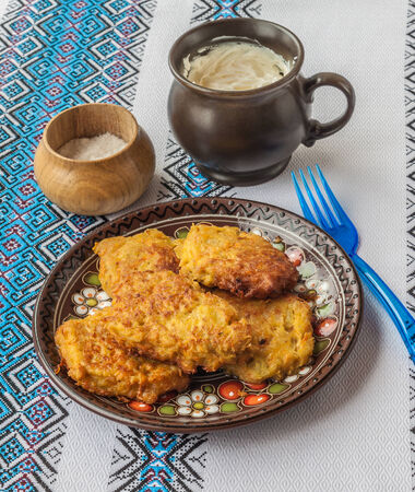 Traditional Ukrainian homemade potato pancakes potato, carrot and pumpkin with sour cream on embroidered tablecloths photo