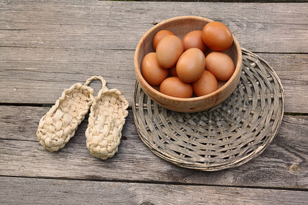 bast: Wooden bowl with the brown eggs  and bast on the table