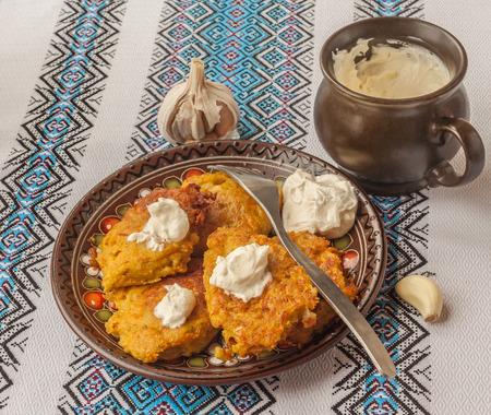 Traditional Ukrainian homemade potato pancakes potato, carrot and pumpkin with sour cream photo