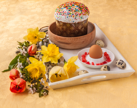 the next life: Easter still life with traditional kulich and by the bouquet  of yellow and red tulips and daffodils next to quail eggs on a white tray Stock Photo