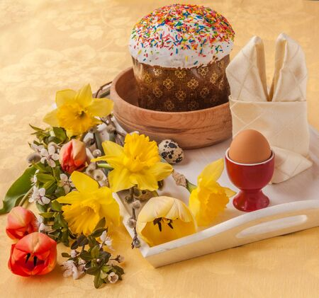 paskha: Easter cake and by the bouquet tulips and daffodils next to quail eggs on a white tray Stock Photo