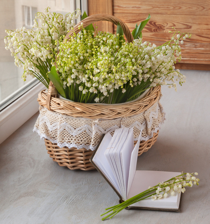 Basket with lilies of the valley (Convallaria majalis) next to notebook with blank pages on o the window