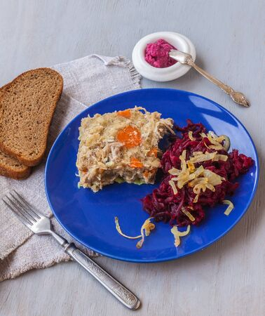 epicure: Plate with aspic and horseradish, grated beets, onions, rye bread on the table