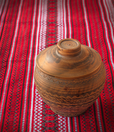 flaxen: Clay pot covered with a lid on the background fabric pattern Ukrainian