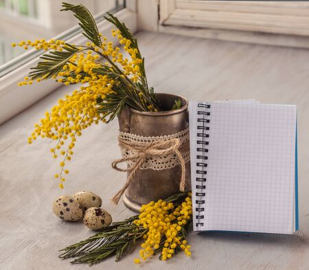 Easter composition with eggs and mimosa on a clean background page notebook photo