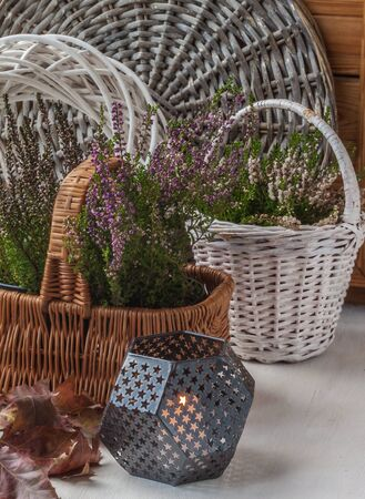 heather: Autumn composition with heather in baskets and burning candle Stock Photo